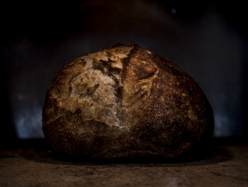 Sourdough bread with dark crust, photo style is chiaro scuro
